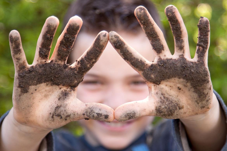 Ein Junge lächelt im Hintergrund, im Vordergrund sind seine mit Erde beschmierten Hände zu sehen.  - Copyright: © Markus Bormann